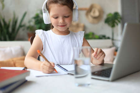 Smiling little girl in headphones handwrite study online using laptop at home, cute happy small child in earphones take Internet web lesson or class on PC
