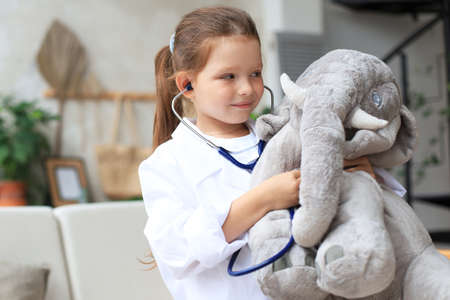 Adorable child dressed as doctor playing with toy elephant, checking its breath with stethoscope