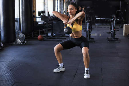 sport woman with kettlebell in the gym