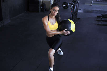 Top view of fit and muscular woman exercising with medicine ball at gym Zdjęcie Seryjne