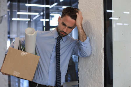 Sad dismissed worker is taking his office supplies with him from office