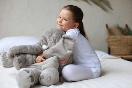 Sweet little girl sitting on her bed at home with toy elephant