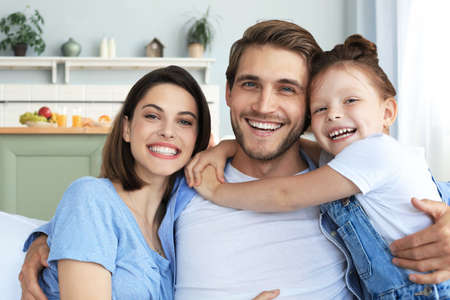 Positive friendly young parents with smiling little daughter sitting on sofa together while relaxing at home on weekend