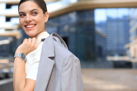 Smiling business woman standing with a jacket over her shoulder near office building