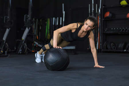 Fit and muscular woman exercising with medicine ball at gym