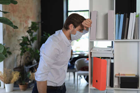 Sad worker in medical mask standing in office
