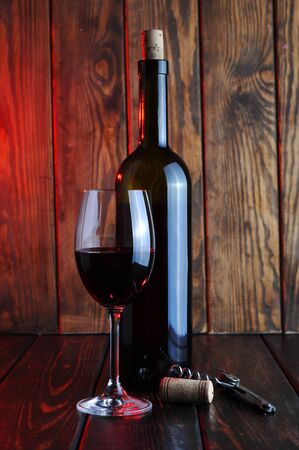 A glass of red wine with a bottle and a candle on a wooden background.