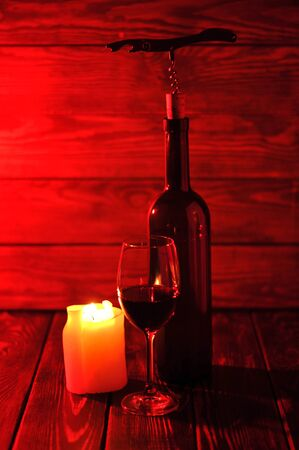 Bottle of red wine with a glass and corkscrew on an old wooden table.Candle light.