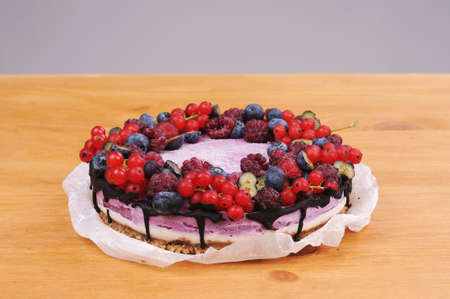 Festive cake, blueberry and blackberry sponge cake with cream cheese inside on a plate on a wooden table, horizontal view from above.