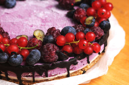 Festive cake, blueberry and blackberry sponge cake with cream cheese inside on a plate on a wooden table, horizontal view from above. Macro photo. Stok Fotoğraf