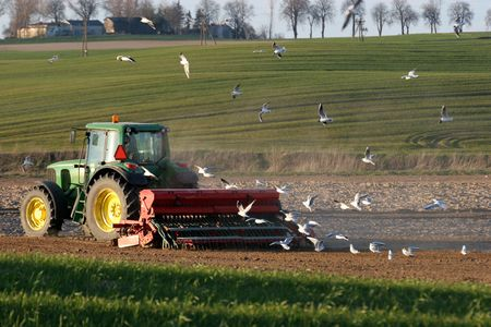 Tractor working on the field. Spring time photo