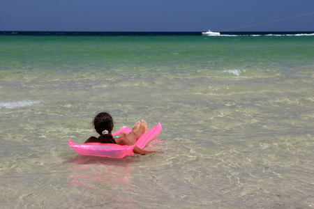 Young girl on pink air-bed in the Mediterranean Sea. Monastir, Tunisia. photo