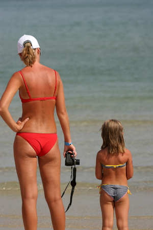 Young woman with her daughter looking at the sea Stock Photo