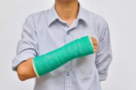 broken wrist: green cast on hand and arm isolated on white background