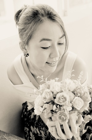 a young asian woman with bouquet smilling, cream tone Stock Photo - 22144486