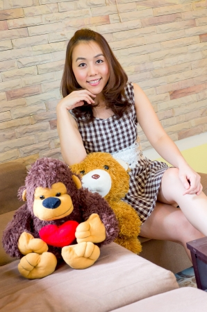 a young asian woman smilling and sitting on couch with monkey and teddy bear photo