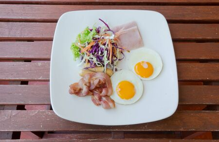 Breakfast with bacon, fried egg, ham, Sausages and fresh vetgetable on wood table  photo