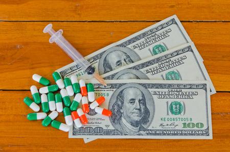 one hundred dollars syringe and capsules on wood background photo