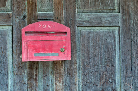 Red wooden mail box on wooden wall. photo