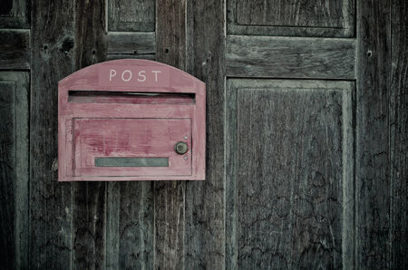 Grunge red wooden mail box on grunge wooden wall  photo