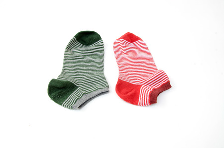 children s feet: green and red striped socks isolated on white