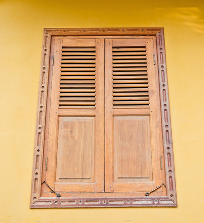 rafter: Wooden window on yellow cement wall. Stock Photo