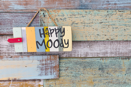 Happy or Moody sign board on wooden vintage background. photo