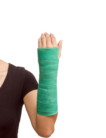 broken arm with green cast on white background. photo
