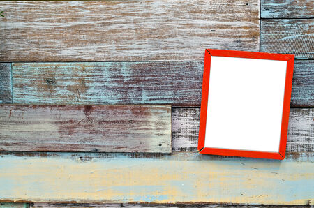 Red wooden frame hanging on a wooden board. photo