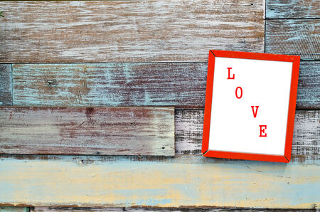 Love red wooden frame hanging on a wooden board. photo