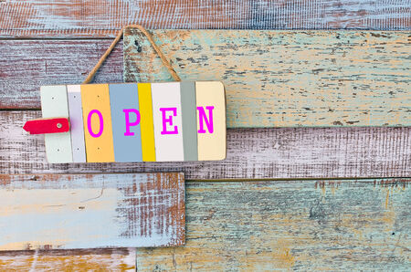 Open sign board on wooden vintage background. photo