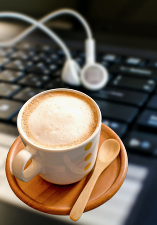 coffee cup with  headphones on laptop. photo