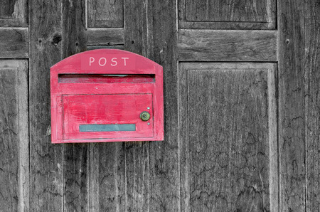 await: Red wooden mail box on wooden wall.