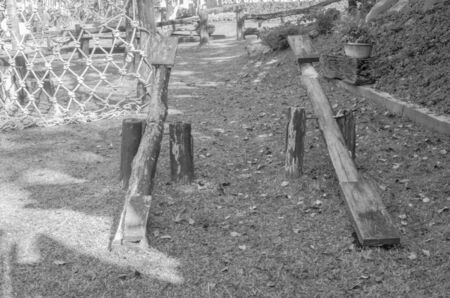 wood playground in green grass field, black and white