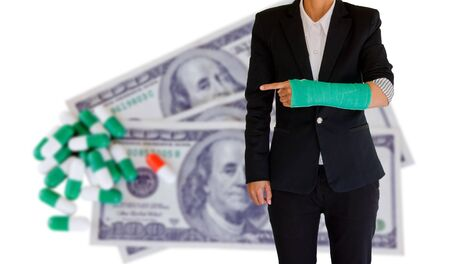 injured businesswoman with green cast on the wrist on banknote and capsules background blur photo