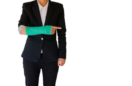 Injured businesswoman with green cast on hand and arm on white background, insurance concept