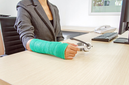 Injured businesswoman with green cast on the wrist holding white headphones on wood table in office background photo