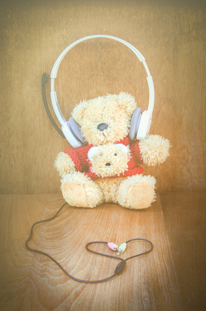 Teddy bear with white headphone and heart shaped cables on wood background photo