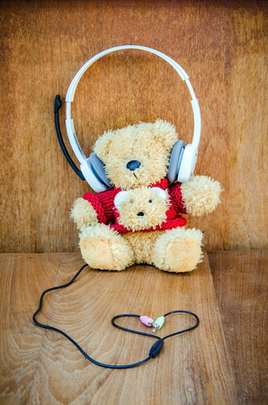 Teddy bear with white headphone and heart shaped cables on wood background
