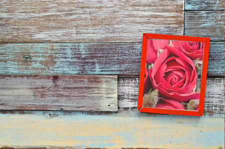 Red rose in wooden frame hanging on a wooden board, Valentines day concept photo