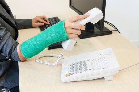 Injured businesswoman with green cast on the wrist holding telephone photo