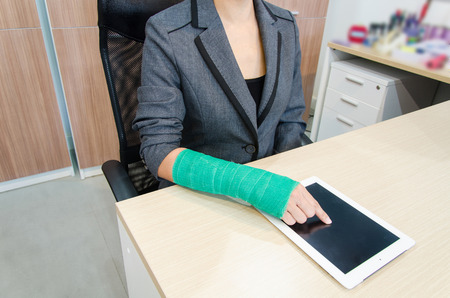Injured businesswoman with broken hand  and green cast on the wrist using tablet computer