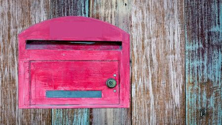 await: red wooden mail box on wooden wall