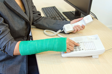 woman dialing phone number: Injured businesswoman with green cast on the wrist pressing number button at office desk