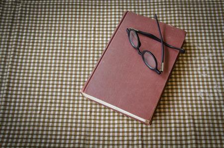 shortsightedness: old book and glasses on tablecloth