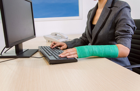 Injured businesswoman hand  typing on computer keyboard