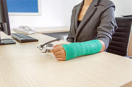 accident patient: Injured businesswoman with green cast on the wrist holding white headphones on wood table in office background