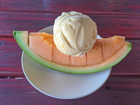 half ball: Vanilla Ice cream scoop on melon slide. Stock Photo