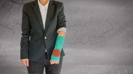 arm pain: injured businesswoman with green cast on hand and arm pain in the joints of the hand