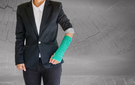 cast: Injured businesswoman with green cast on hand and arm on blurred abstract background